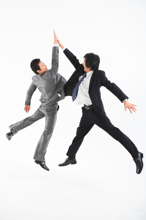Two Asian businessmen putting posing in the studio - isolated on white