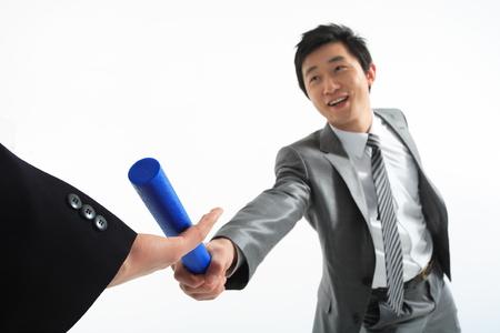Aziatische zakenman die het relaisbaton passeert - geïsoleerd op wit Stockfoto