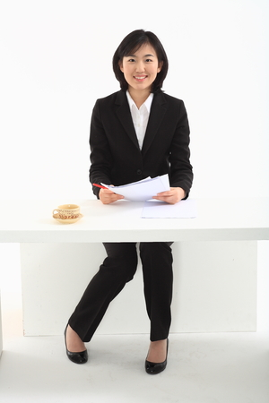 Young Asian business woman sitting in the desk - isolated on white