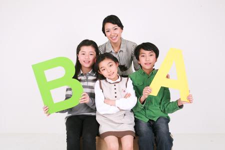 Een vrouwelijke leraar en kinderen die alfabet A en B-vormige tekens steunen - die op wit worden geïsoleerd