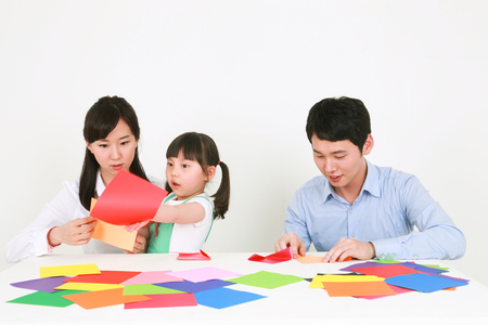 Adults and a little girl folding colored paper - isolated on white