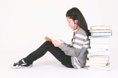 A girl reading a book - isolated on white