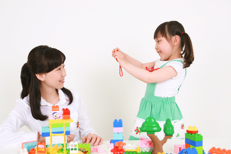 A woman and a little girl playing with blocks - isolated on white Stock Photo