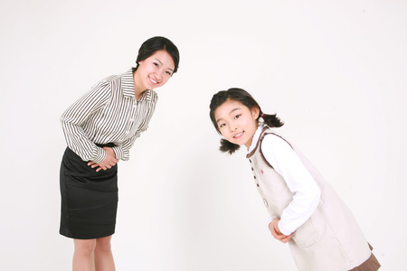 bowing head: An asian girl and woman bowing their head in greeting- isolated on white Stock Photo