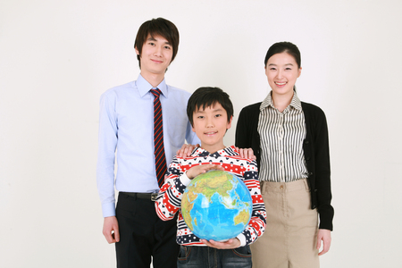 A boy holding up a globe standing with two teachers