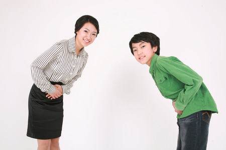 bowing head: An asian boy and woman bowing their head in greeting- isolated on white Stock Photo