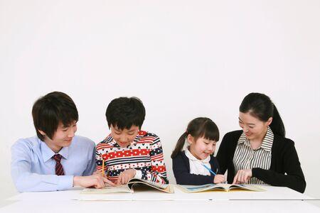 Two teachers and two kids studying Redakční