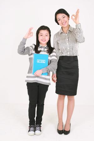 zapatos escolares: Una niña asiática y una mujer stading con sonrisa - aislados en blanco Editorial
