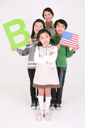 A teacher and three kids holding up an American flag and an alphabet B shaped sign - isolated on white