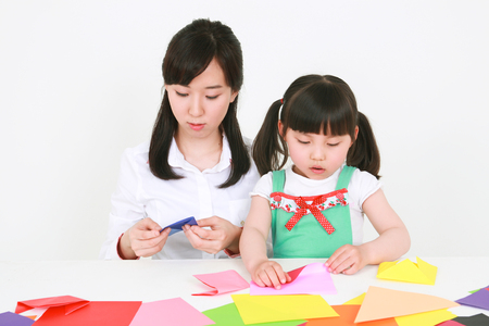 A woman and a little girl folding colored paper - isolated on white