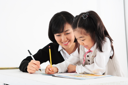 even: An smiling asian girl studying with a teacher - isolated on white