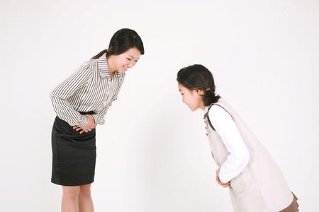 아시아 여자와 인사말 - 화이트 격리에 그들의 머리를 숙이고하는 여자