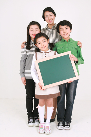 An asian woman and three kids standing with smile - isolated on white Editorial