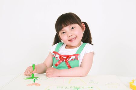 Little Asian girl drawing with crayons - isolated on white
