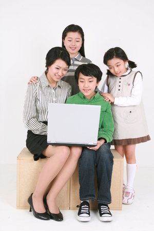 A teacher and three kids looking at a laptop computer - isolated on white Stock Photo