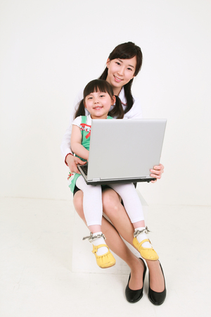 A woman and a little girl looking at a laptop computer - isolated on white