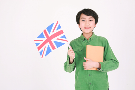 A boy holing up a Union jack and book - isolated on white Banco de Imagens