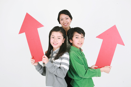 An asian woman and two kids standing with smile - isolated on white