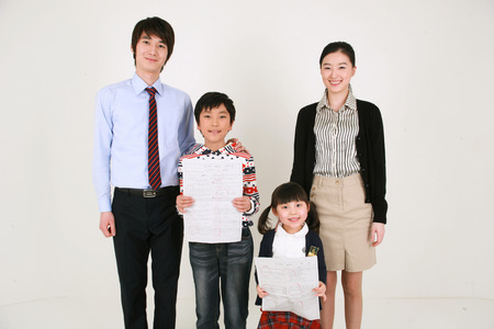Two teachers and two little boys holding up a test paper Banco de Imagens