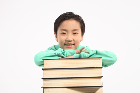 beside: A little girl standing beside piles of books - isolated on white Stock Photo