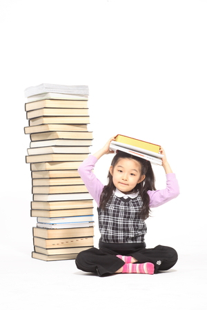 beside: A little girl sitting beside piles of books - isolated on white