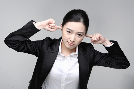 irritated: Young Asian businesswoman posing in the studio - isolated on white Stock Photo