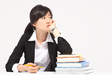 A asian woman studying and being in deep thought - isolated on white