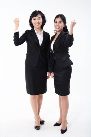 nobleness: Two Asian business women posing in the studio - isolated on white