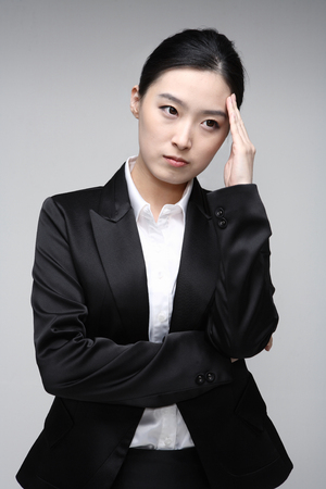 headaches: Young Asian businesswoman posing in the studio - isolated on white Stock Photo