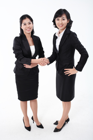 associate: Two Asian business women posing in the studio - isolated on white