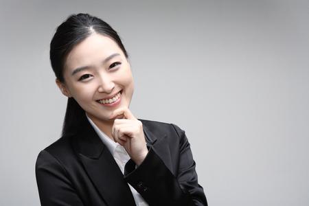 Het jonge Aziatische onderneemster stellen in de studio - die op wit wordt geïsoleerd