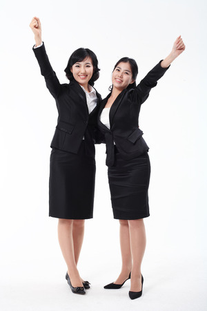 hurray: Two Asian business women posing in the studio - isolated on white