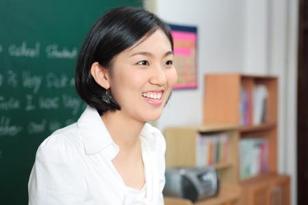 A teacher posing in a high school classroom