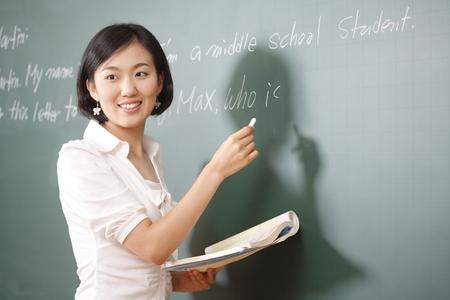 Um professor que está posando em uma sala de aula do ensino médio Foto de archivo - 80480750