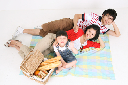 Young asian family picnic - isolated on white