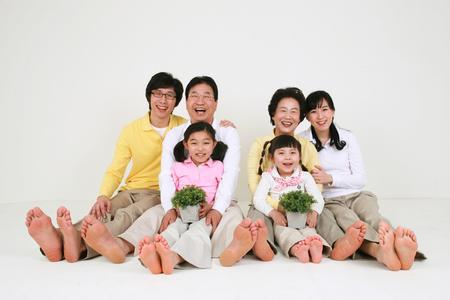 Een Aziatische grote familie kleedde casual - geïsoleerd op wit Stockfoto