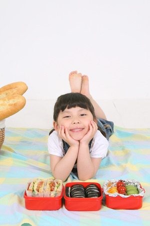 Asian little girl lying down beside picnic basket  - isolated on white