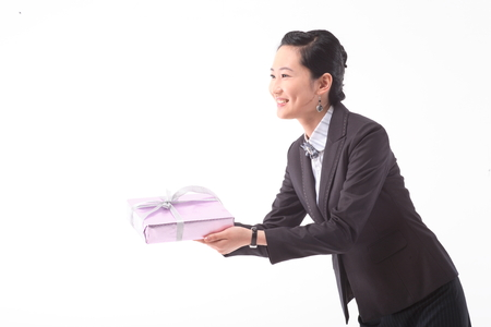 Asian businesswoman posing with a gift box - isolated on white