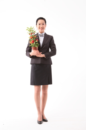 Asian businesswoman posing with a potted apple tree - isolated on white