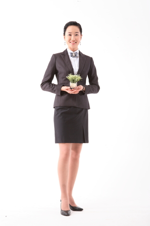 Asian businesswoman posing with a little potted plant - isolated on white