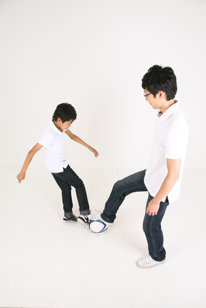 Asian boy and man playing soccer - isolated on white