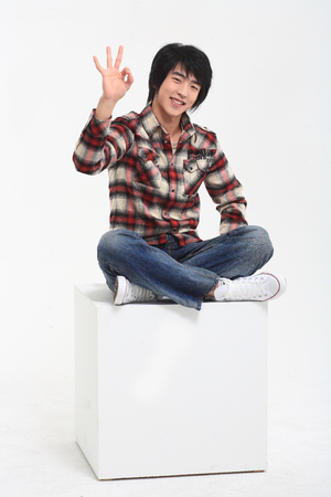 Young asian man sitting in studio - isolated on white