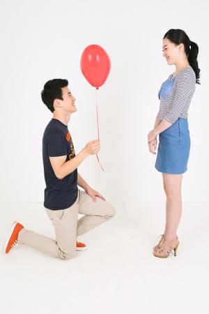Asian couple celebrating in studio - isolated on white