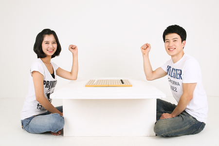 Asian couple playing game in studio - isolated on white