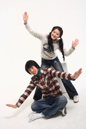 spolužák: Young asian couple sitting in studio - isolated on white Reklamní fotografie