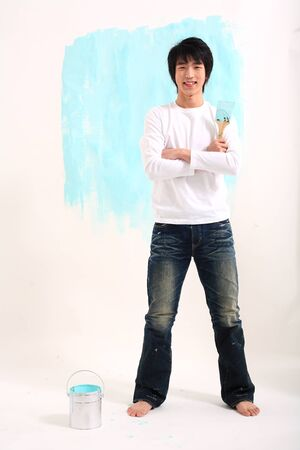 Young asian man painting in studio - isolated on white