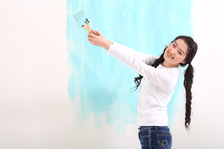 Young asian woman painting in studio - isolated on white