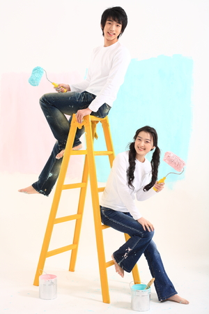 Young asian couple painting in studio - isolated on white