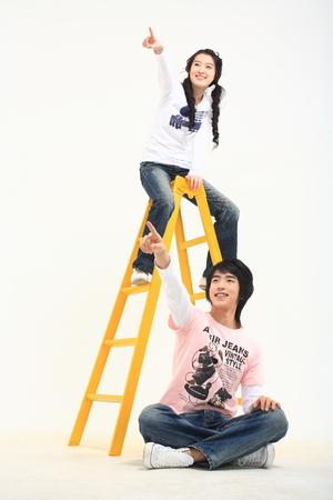 スタジオ - 白で隔離の若いアジア学生カップル 写真素材