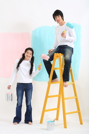 roller: Young asian couple painting in studio - isolated on white